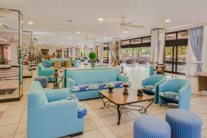 Sofás do lobby de entrada com detalhes na cor azul e mesa de centro