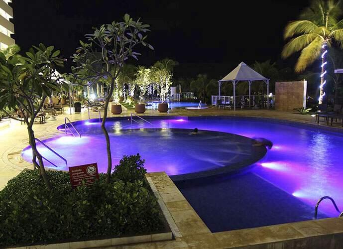 Toda estrutura e lazer no período da noite como mostra piscina iluminada